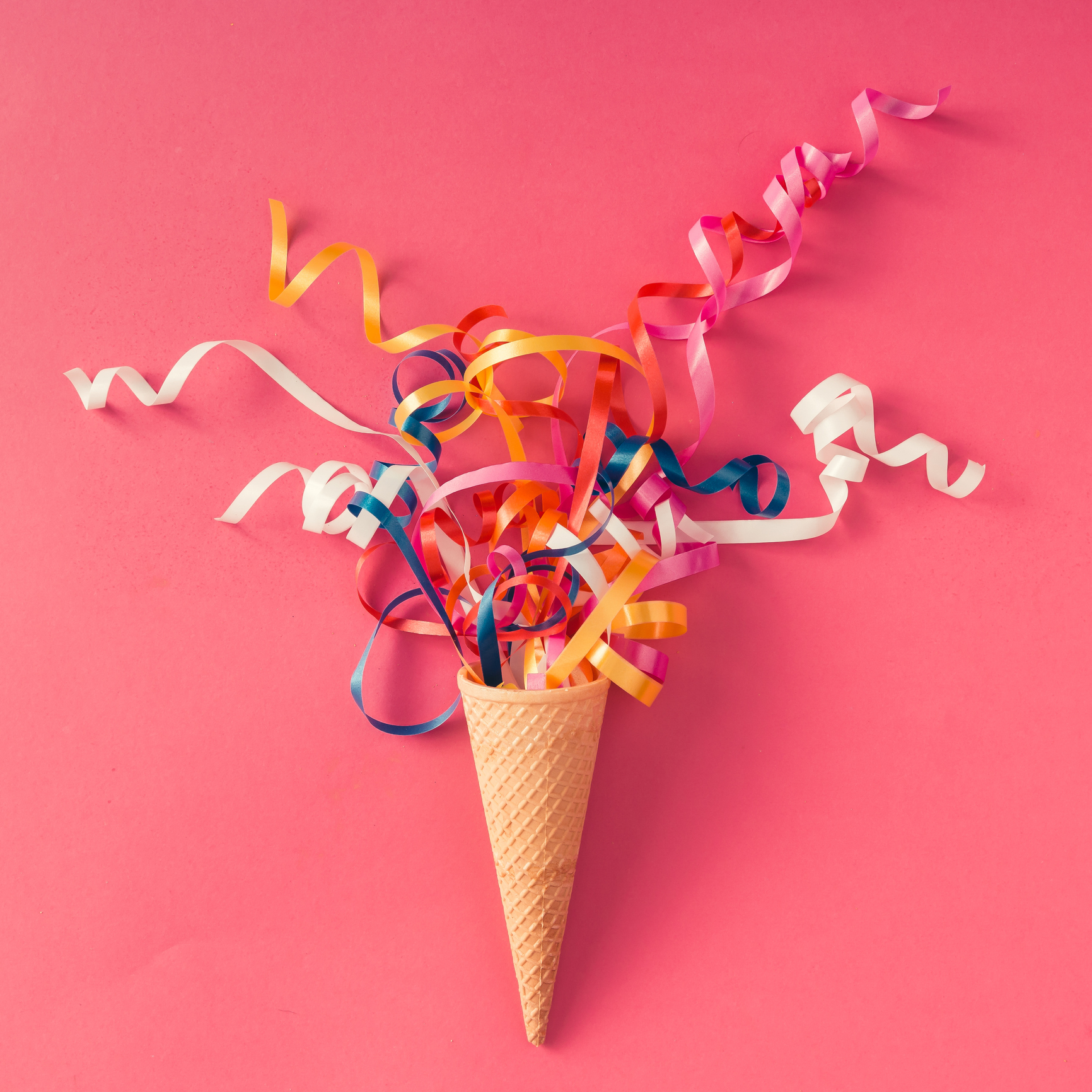 Ribbons coming out of an ice cream cone on a pink background