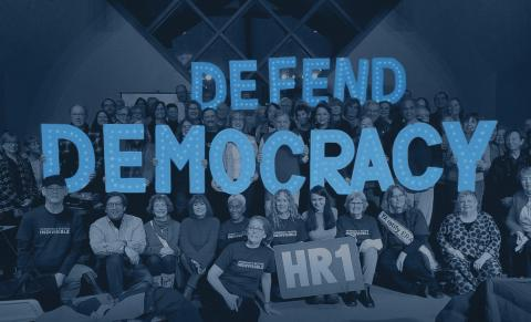 """Local Indivisible group holding letters that spell the phrase """"Defend Democracy."""""""