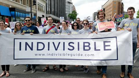 Image of Indivisible staff at a rally holding an Indivisible banner