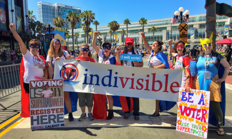 Image of Indepedent Indivisible group members in capes and costumes holding their banner