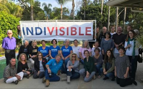 A large group of Indivisible members sit in front of an Indivisible banner on a sunny day near some palm trees in Southern California.